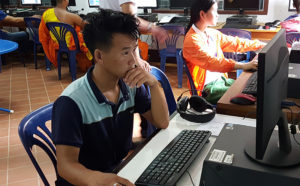 Students complete computer exam in Laos school